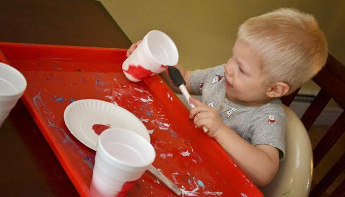 Ребенок раскрашивает одноразовый стакан